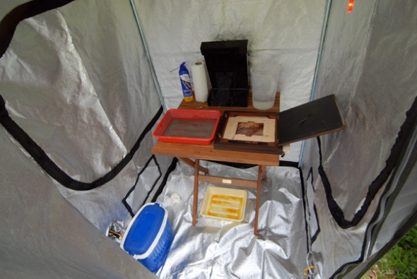 Inside of the tent: Left on the ground is the cooling box which keeps the developer and collodion with a frozen pack, on the table at the back is the silver bath with on the left compressed air can, on the right is my back, on the left my developer tray, at the bottom my collodion pouring tray which is only on the table when needed, red LED light you can see glowing on the approx. upper right